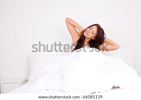 pretty happy girl waking up in the morning and stretching - stock photo
