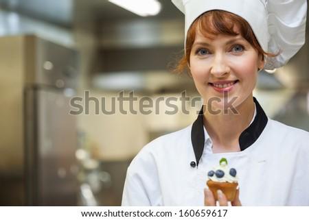 Pretty happy head chef holding blueberry dessert in professional kitchen - stock photo