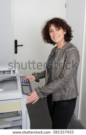 Pretty happy woman using a copy machine at work - stock photo