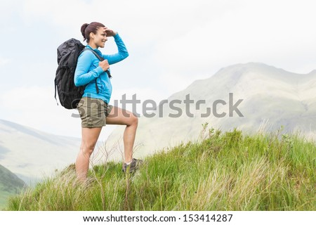 Pretty hiker with backpack walking uphill and looking ahead in the countryside - stock photo
