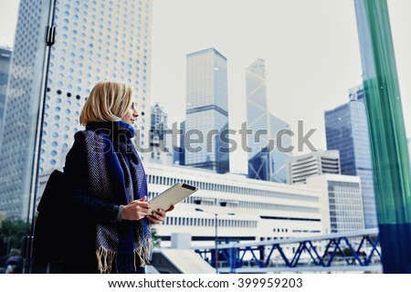 Pretty hipster girl dressed in spring clothes is holding portable touch pad and looking into the window on active life of New York Metropolitan city, while standing in skyscraper interior. Copy space - stock photo