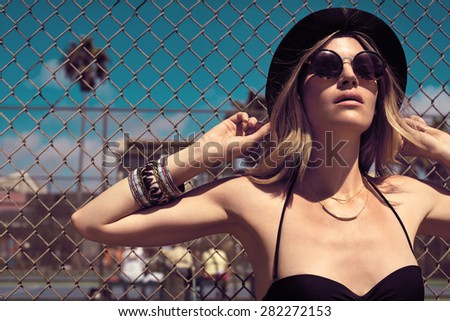 Pretty hipster girl in sunglasses, jeans shorts, black bikini and a hat. Close-up lifestyle outdoor portrait - stock photo