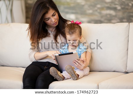 Pretty Hispanic babysitter using a tablet computer with a little girl - stock photo