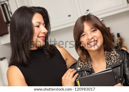 Pretty Hispanic Girl and Mother Getting Ready for School in the Kitchen. - stock photo