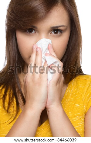 Pretty hispanic girl blowing nose - stock photo