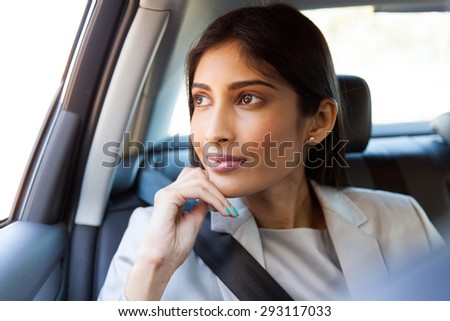 pretty indian business executive daydreaming in a car - stock photo