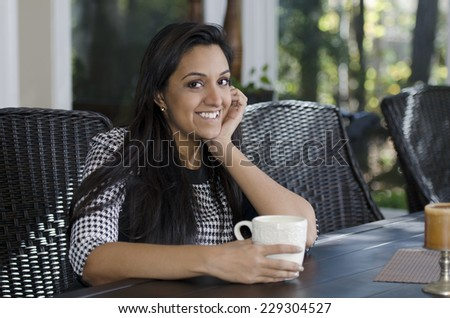 Pretty Indian woman relaxing as she drinks her tea - stock photo