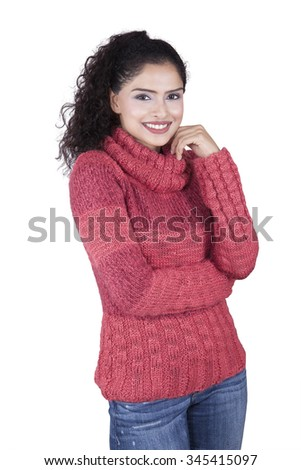 Pretty indian woman standing in the studio while wearing winter clothes and smiling at the camera, isolated on white background - stock photo