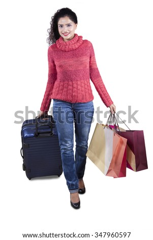 Pretty indian woman walking in the studio while wearing warm clothes and carrying shopping bags with suitcase - stock photo