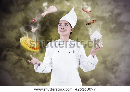 Pretty indian woman wearing a cooking clothes and making food with magic - stock photo
