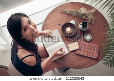 Pretty Japanese young woman looking at the camera while writing in the exercise book, view from above - stock photo