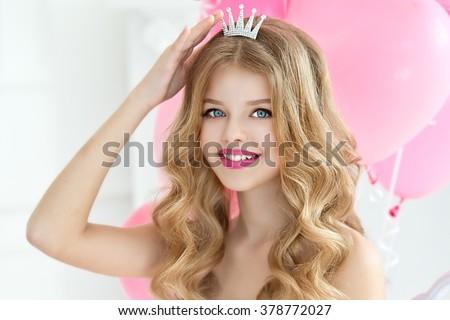 Pretty joyful girl on birthday party. Princess. Barbie girl.Smiling Girl with tiara crown - stock photo
