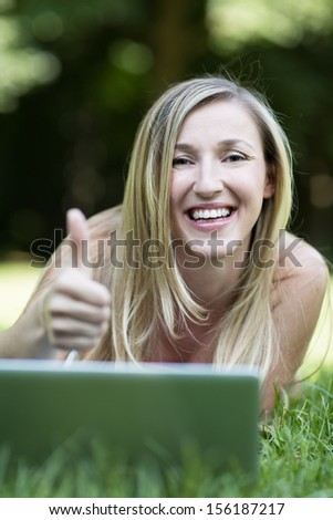 Pretty joyful young blond woman with a friendly smile working with her laptop lying on the grass in a park giving a thumbs up of approval - stock photo