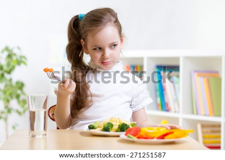 pretty kid girl refusing to eat her dinner healthy vegetables - stock photo