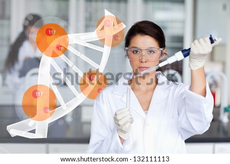 Pretty lab worker adding chemical to test tube with dna helix interface - stock photo
