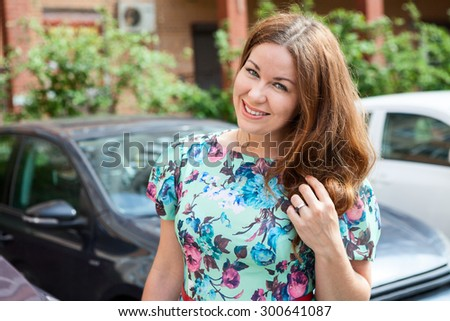 Pretty lady a driver standing behind the car at parking lot, summer day - stock photo