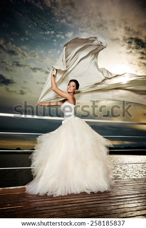 Pretty lady in a wedding dress on deck. - stock photo