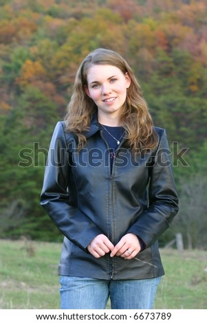 Pretty lady in black leather jacket against a fall background - stock photo
