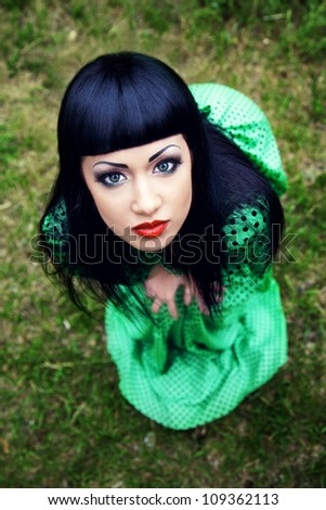 Pretty lady in green dress outdoors - stock photo