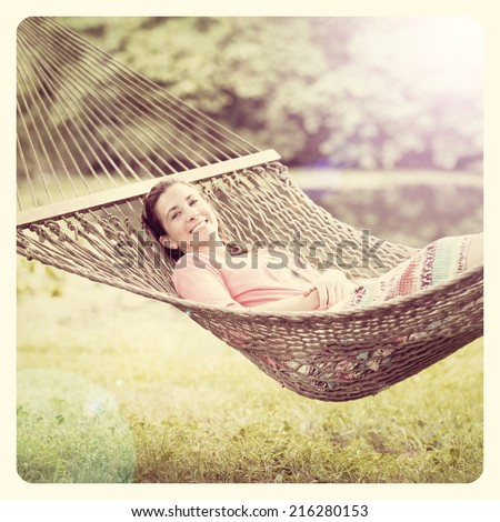 Pretty lady lying in a hammock with Instagram effect filter  - stock photo