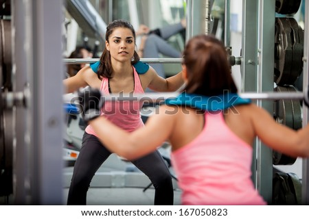 Pretty Latin brunette doing some squats with a barbell and focusing on her routine - stock photo