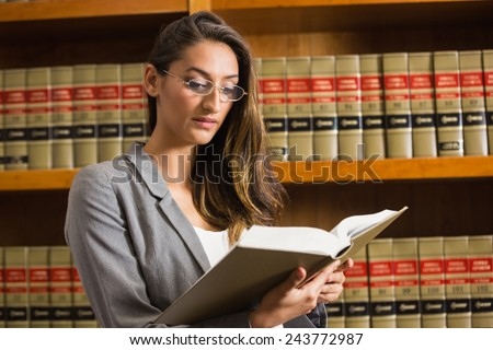 Pretty lawyer reading in the law library at the university - stock photo