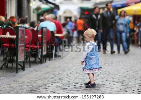Pretty little baby girl standing on a busy crowded street in a center of big city, reading big menu poster outside of restaurant with summer terrace, at background people walking and relaxing in cafes - stock photo