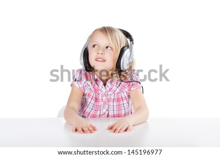 Pretty little blond girl wearing a set of headphones which are too large for her staring up into the air as she listens to the music enjoying her leisure time - stock photo