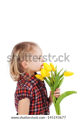 Pretty little blond girl with a serious expression posing with a bouquet of fresh yellow tulips held to her chin, isolated on white - stock photo