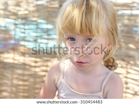 Pretty little blond girl with a sulky expression looking up at the camera as she plays on her beach in dappled sunlight - stock photo