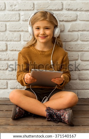 Pretty little blonde girl listening to music and using tablet while sitting cross-legged against white brick wall - stock photo