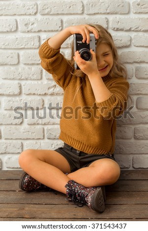 Pretty little blonde girl making a photo while sitting cross-legged against white brick wall - stock photo