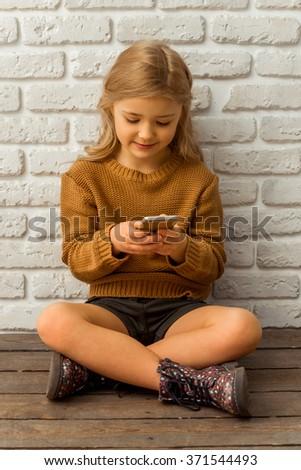Pretty little blonde girl using smartphone while sitting cross-legged against white brick wall - stock photo