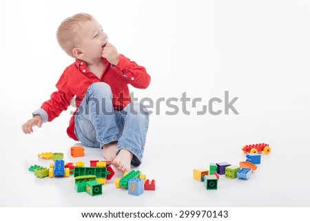 Pretty little boy is sitting on flooring and playing with toys. He is looking aside with joy and smiling. Isolated on background and copy space in right side - stock photo
