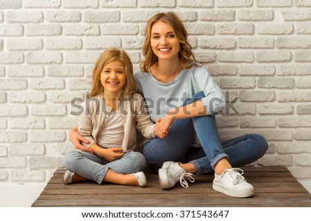 Pretty little girl and her beautiful young mother, looking in camera and smiling while sitting against white brick wall - stock photo