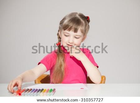 Pretty little girl choosing a marker, neutral background - stock photo