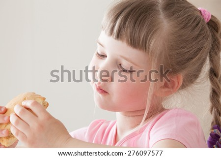 Pretty little girl eating a doughnut with enjoyment - stock photo