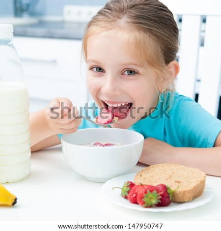 pretty little girl eating cereal and strawberries in the white kitchen - stock photo