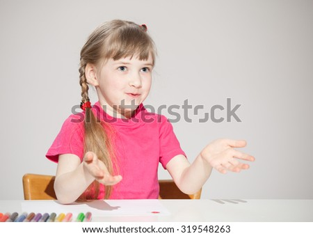 Pretty little girl explaining something and sitting at the table - stock photo