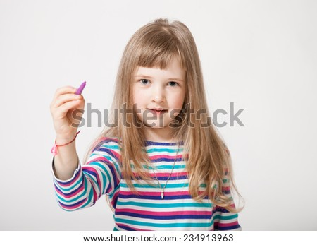 Pretty little girl holding a purple felt-tip pen and drawing something, white background - stock photo