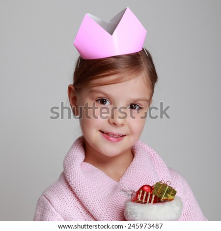 pretty little girl holding Christmas boots with gifts for Christmas - stock photo