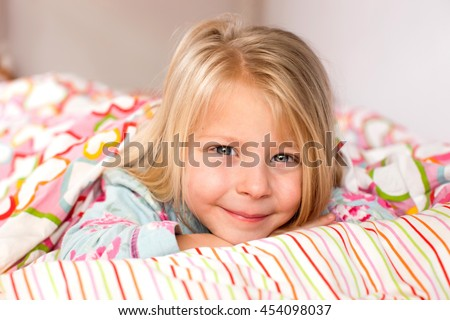 Pretty little girl in pajamas lying in bed in the morning - stock photo