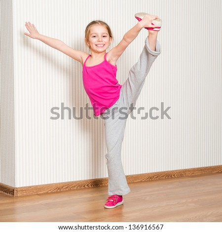 pretty little girl in pink engaged in fitness at home - stock photo