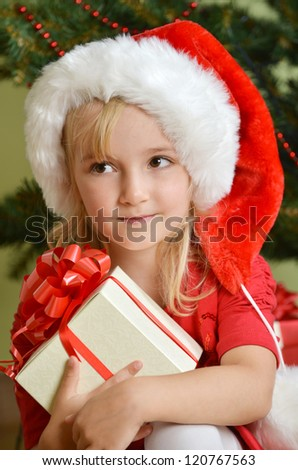 Pretty little girl  in santa cap near Cristmas tree - stock photo