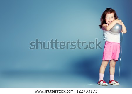 Pretty little girl over grey background. - stock photo