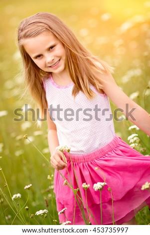 Pretty little girl picking flowers - stock photo