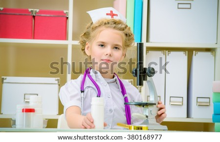 Pretty little girl playing a doctor at home. Different occupations. Children's Health, Pediatrics. - stock photo