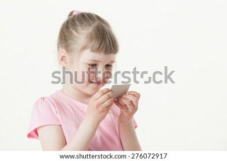Pretty little girl reading the text on a card, white background - stock photo