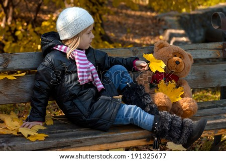 Pretty little girl relax on beauty autumn landscape background - stock photo