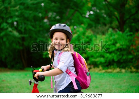 Pretty little girl ride with bicycle in summer park - stock photo